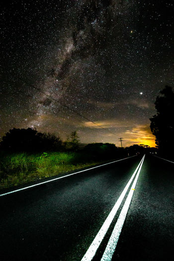 Diminishing Perspective Of Empty Road Against Star Field At Night