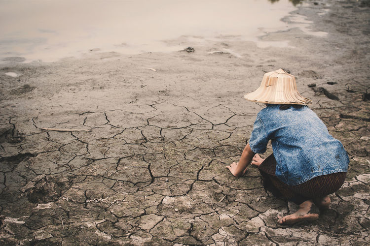 Rear view of girl kneeling on drought field