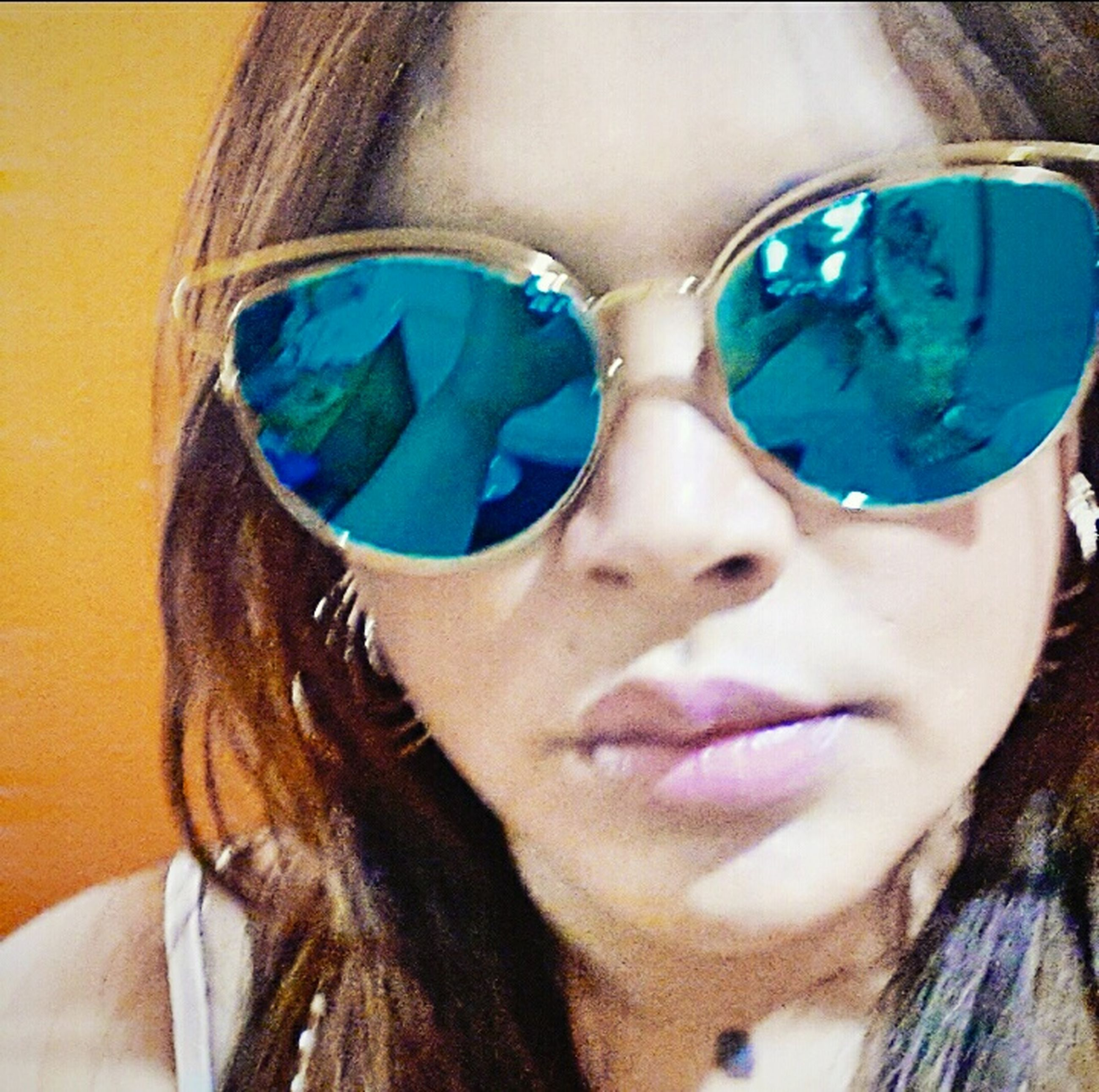 headshot, looking at camera, portrait, person, young adult, lifestyles, close-up, leisure activity, front view, young women, human face, sunglasses, long hair, head and shoulders, indoors, blue, focus on foreground, smiling