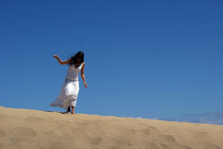 Full length of woman walking on sand at desert against clear sky