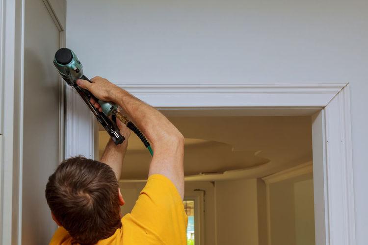 Rear view of man using nail gun on wall at home