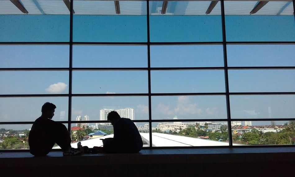 EyeEm Selects Two Teenage Boys Having A Break At The Terminal Silhouette Window Indoors  Two People Technology Day People Togetherness Adult City Cityscape Sky Nature Greenhouse Sea Adults Only EyeEmNewHere Train Station Malaysia Thank You My Friends 😊 Kedah Malaysia