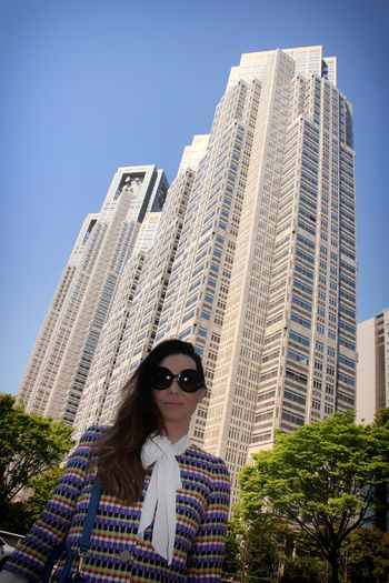 Low angle portrait of smiling young woman standing in city