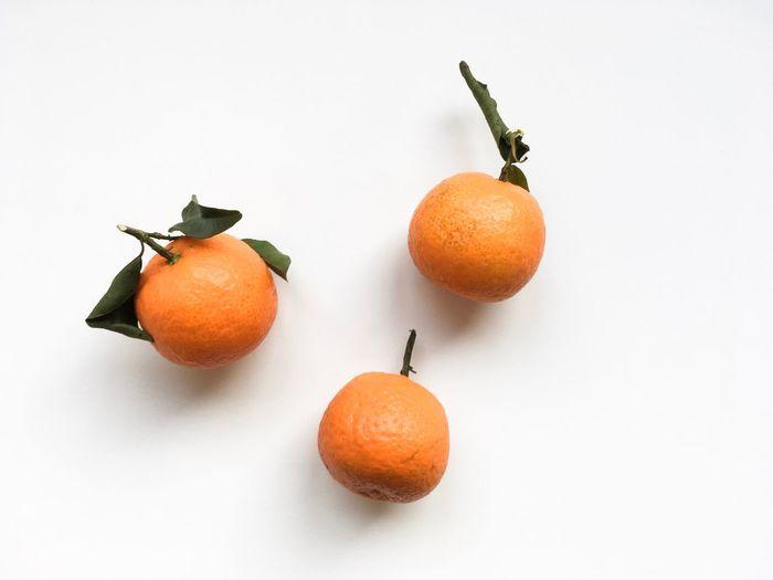 Close-up of orange fruits on white background