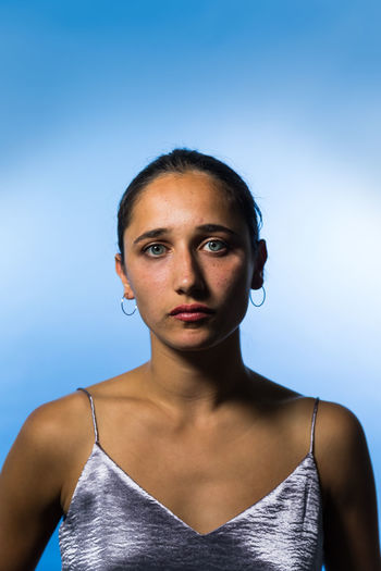 Studio shot of a young woman on mixed race ethnicity. Young Woman Mixed Race Person Indian Medium Shot Studio Shot Tanned Tank Top Beautiful Woman Portrait Front View Blue Background One Person Young Adult Natural Beauty Indoors  Studio Lighting Looking At Camera Colored Background Blue Serious Beauty Sleeveless Top