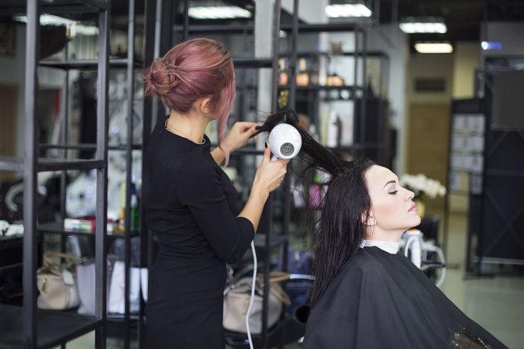Hairdresser combing hair of customer at salon