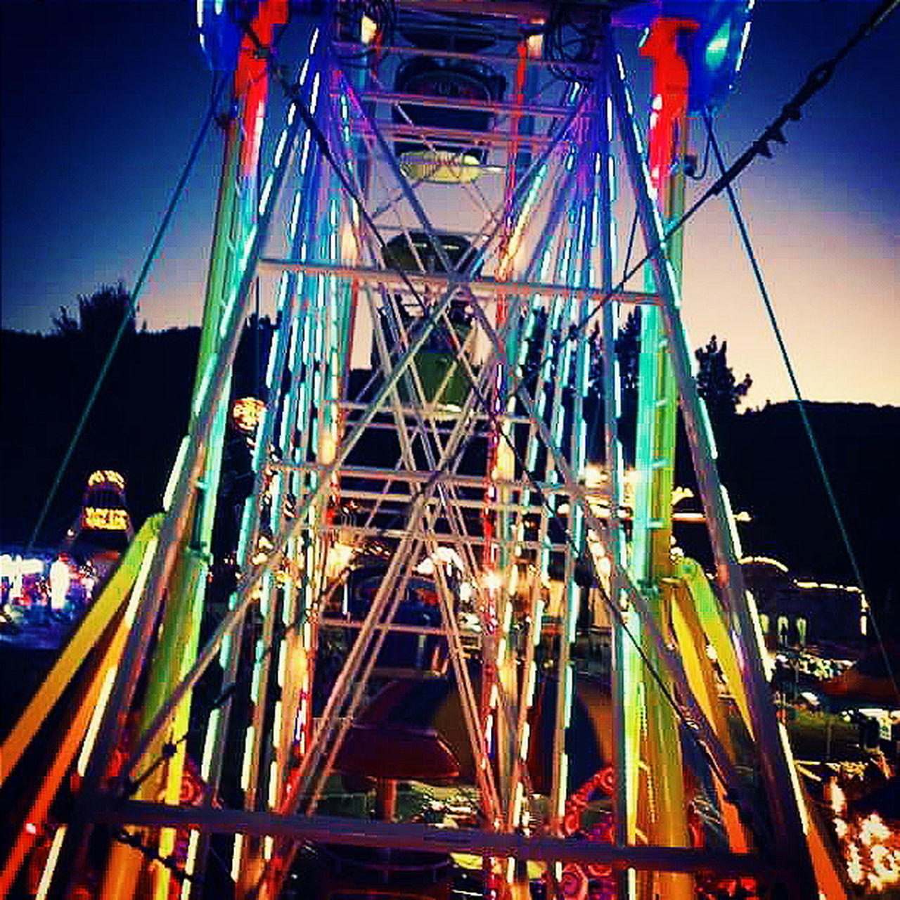 amusement park, arts culture and entertainment, amusement park ride, night, multi colored, illuminated, ferris wheel, built structure, low angle view, outdoors, no people, sky, architecture