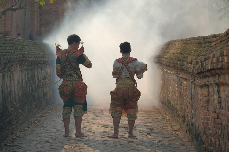 Rear view of men wearing traditional clothing standing on footpath