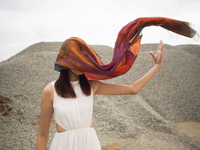 Woman with headscarf waving against heap of stones