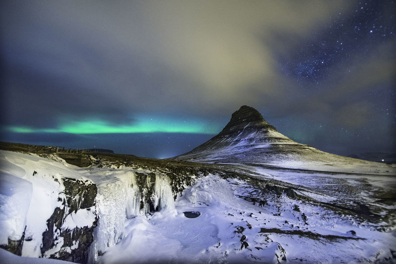 Colorful Aurora Borealis or better known as The Northern Lights and winter milky way over Kirkjufell, Iceland with starry night milky way. Aurora Borealis Kirkjufell Beauty In Nature Cloud - Sky Cold Temperature Environment Frozen Idyllic Landscape Milky Way Mountain Mountain Peak Nature Night No People Non-urban Scene Power In Nature Scenics - Nature Sky Snow Snowcapped Mountain Starry Night Tranquil Scene Tranquility Winter