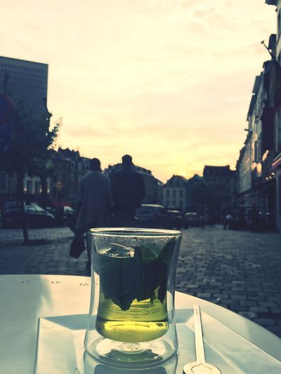 View of drink on table in city at sunset