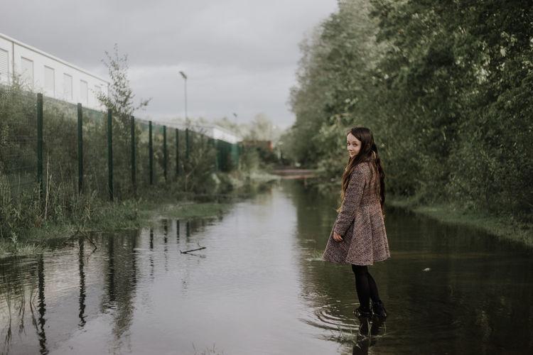 Woman walking by lake against sky