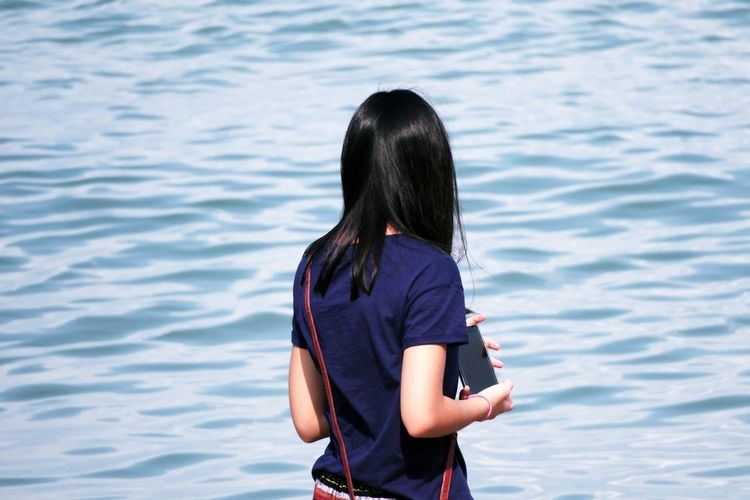 Rear view of woman holding mobile phone while standing by sea