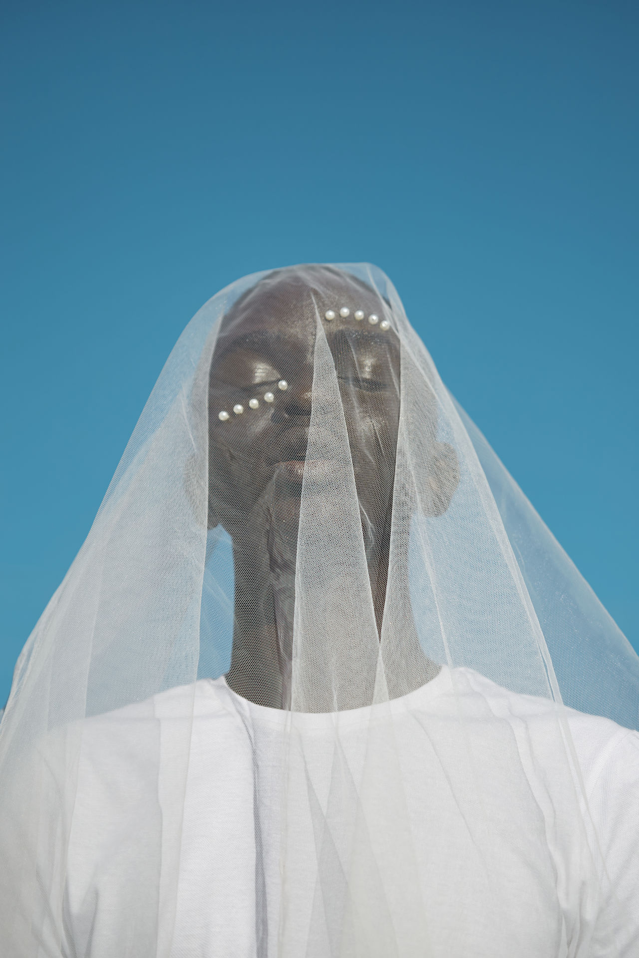 LOW ANGLE VIEW OF MAN COVERING FACE AGAINST BLUE SKY