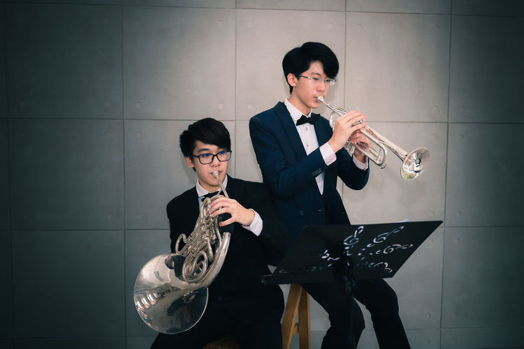 Classics musician Musical Instrument Holding Young Adult Two People Music Young Women Indoors  Males  Musician Front View Togetherness Artist Real People Glasses Playing Men Wall - Building Feature Formalwear Adult Clothing Trumpet