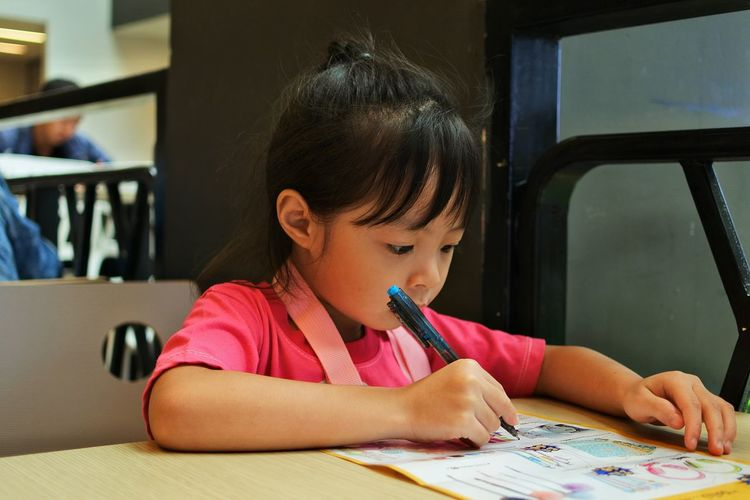 Close-Up Of Girl Drawing At Table