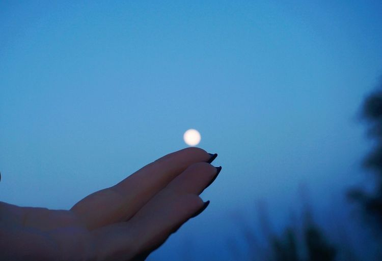 Close-up of hand holding moon against blue sky