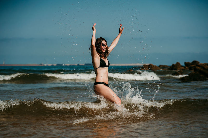 Full length of young woman at beach against sky