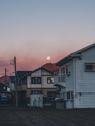 Houses and buildings against sky at sunset