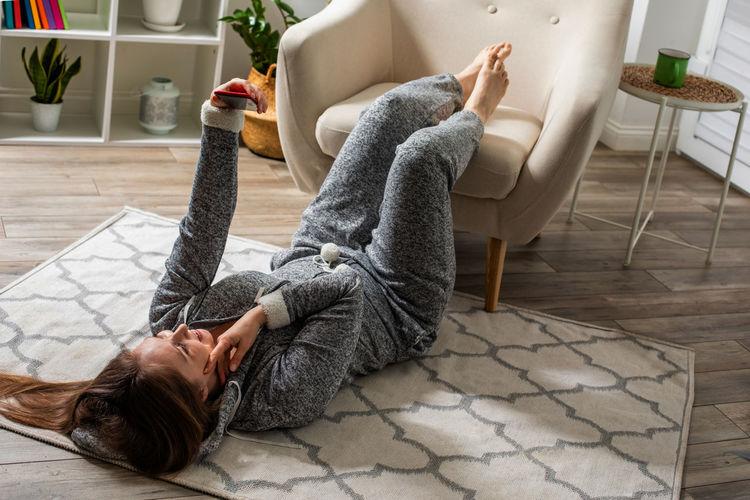 High angle view of woman lying on sofa at home