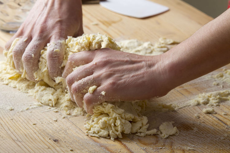 Close-up of hands kneading dough