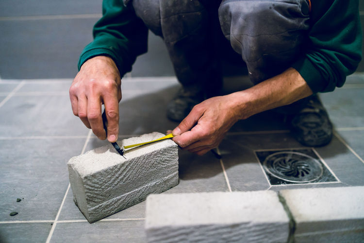 Low section of man marking on brick in bathroom