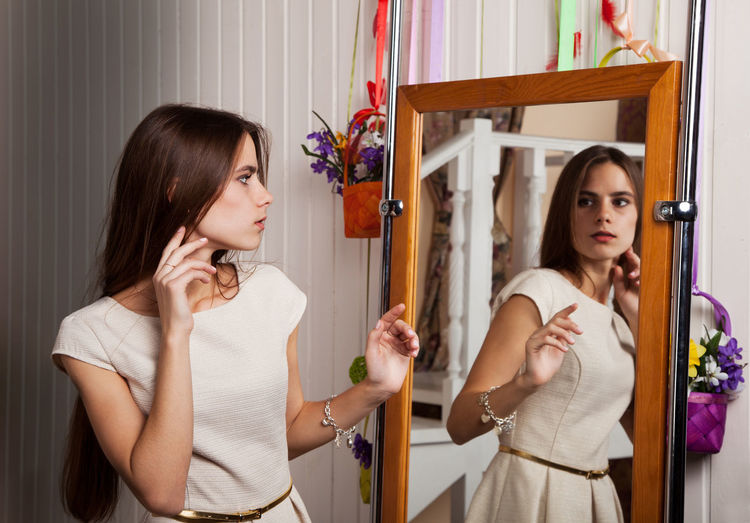 Suspicious Young Woman Looking In Mirror At Home