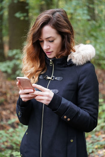 Young woman using mobile phone at park