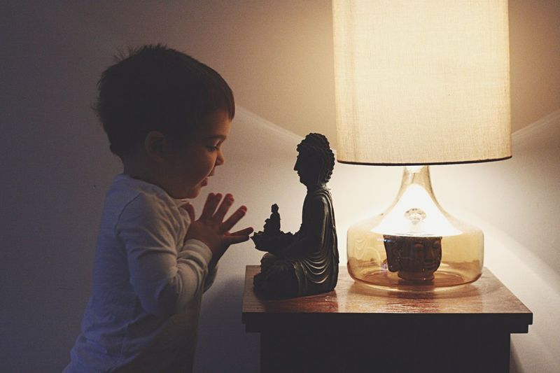 Side view of boy praying to buddha statue by illuminated lamp shade at home