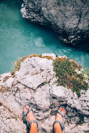 Beauty In Nature Body Part Cliff Day High Angle View Human Body Part Lifestyles Low Section Nature One Person Outdoors Personal Perspective Real People Rock Rock - Object Rock Formation Sea Solid Water