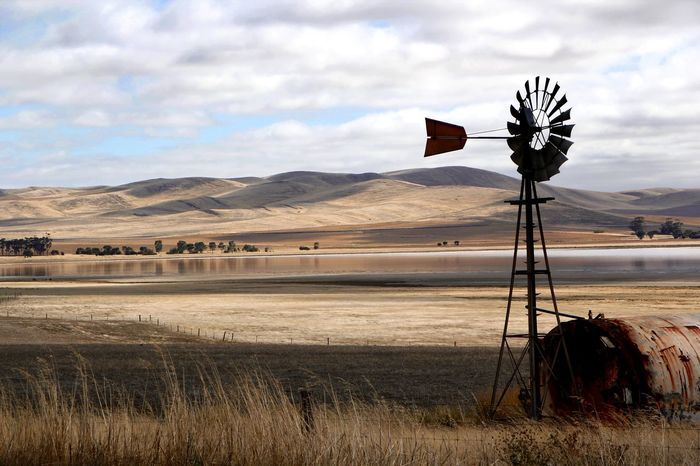 Solitary water vane against storm covered hills and lake in South Australia Alternative Energy Australian Landscape Beauty In Nature Cloud - Sky Day Field Grass Lake Landscape Nature No People Outdoors Rural Scene Scenics Sky Tranquil Scene Tranquility Water Pump Water Vane Wind Power