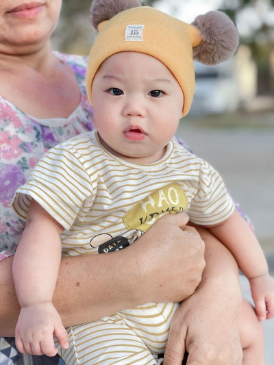 Cute baby boy sitting outdoors