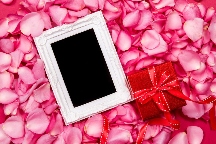 Directly above shot of gift box and blank picture frame on rose petals