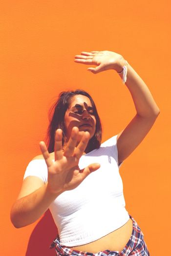 Young Woman Showing Stop Gesture While Standing By Orange Wall