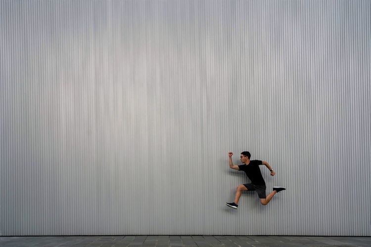 Side view of young man running against wall