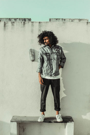 Full length portrait of young man standing against wall
