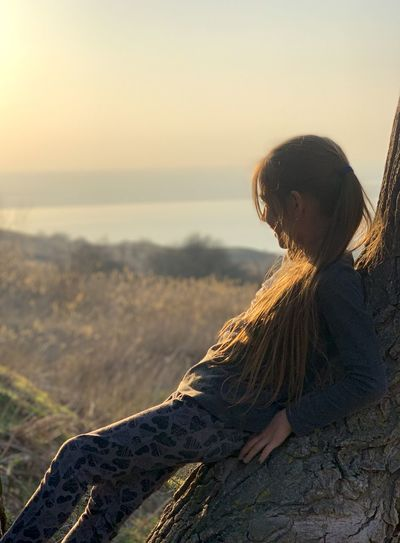 Side view of girl leaning on tree trunk while looking away outdoors
