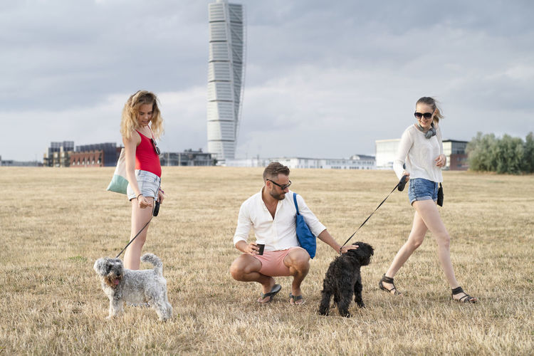 Group of people with dog against sky