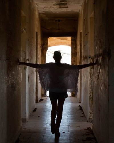 Rear view of silhouette woman standing in abandoned building corridor