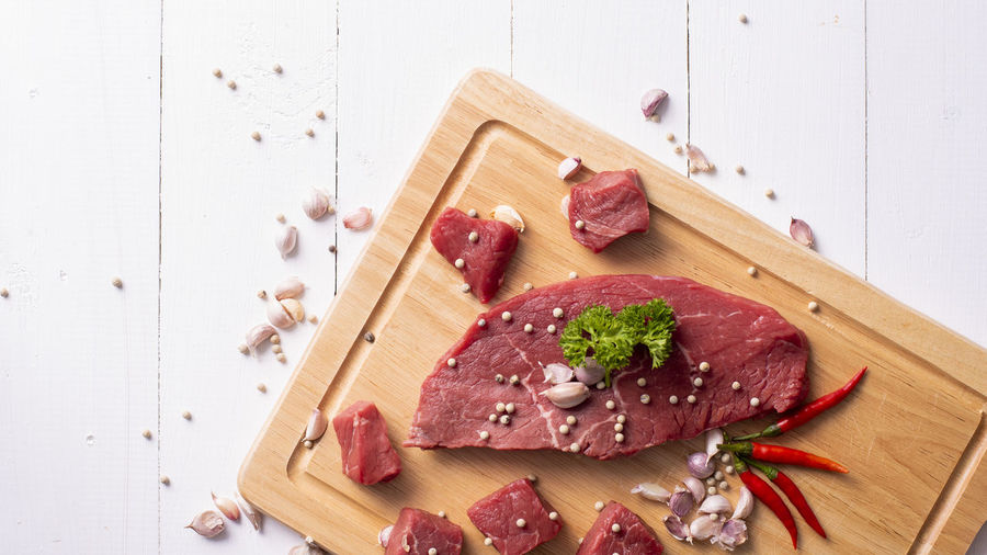 High angle view of chopped meat with spices on cutting board