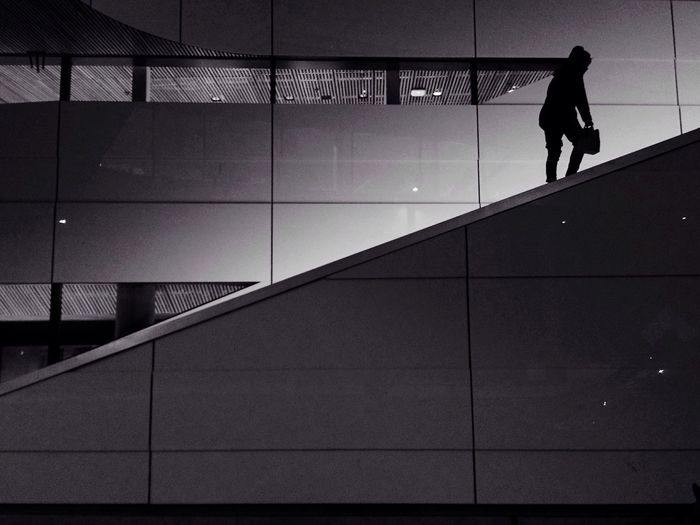Silhouette Person Walking On Staircase Against Wall