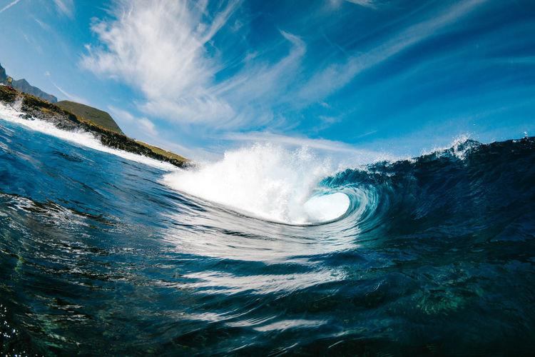 Waves in sea against blue sky