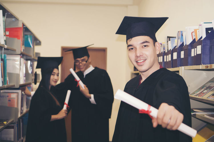 Portrait of smiling young man in graduation gown standing in library