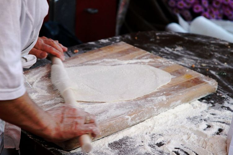 Midsection Of Chef Rolling Dough On Board