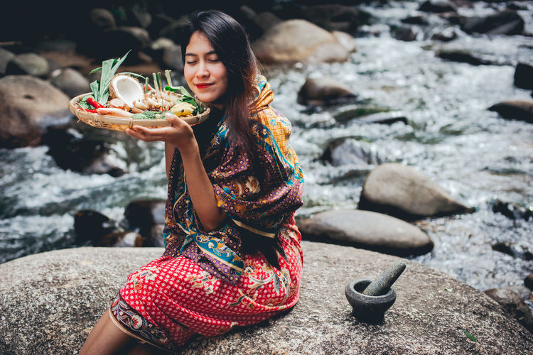 Smiling woman holding fresh food in bucket while sitting on rock amidst river