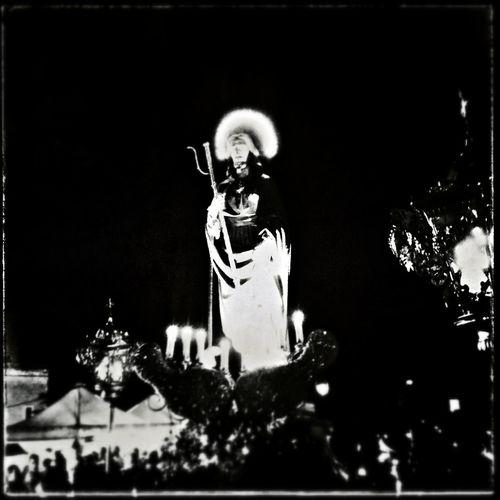 Statue against illuminated trees at night