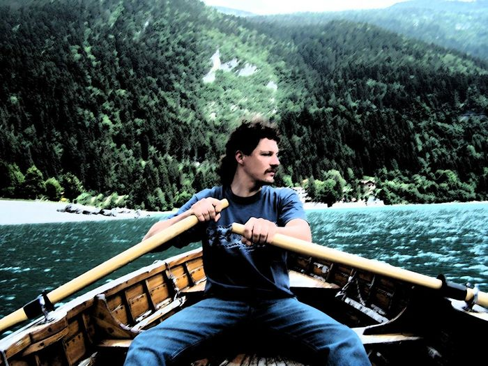 Young man sitting in boat on lake