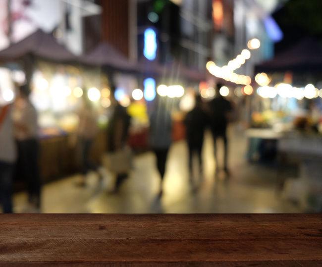 Defocused image of people walking on illuminated street at night