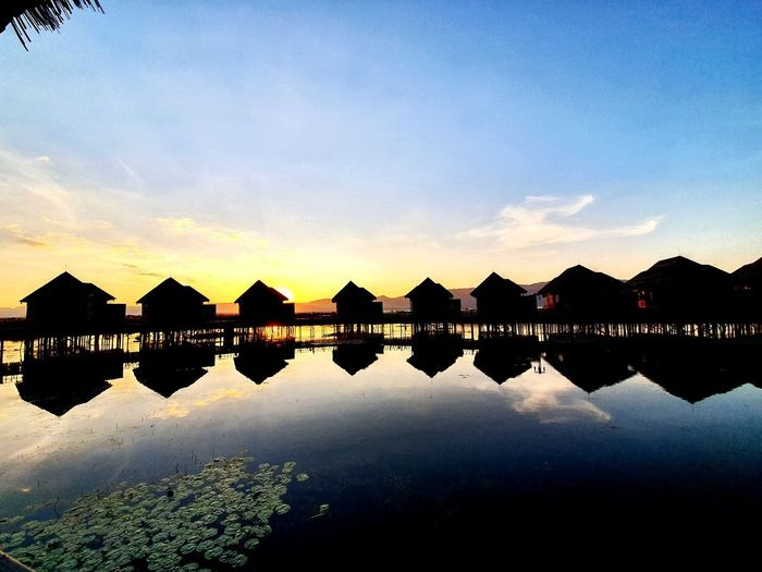Scenic view of lake by silhouette buildings against sky during sunset