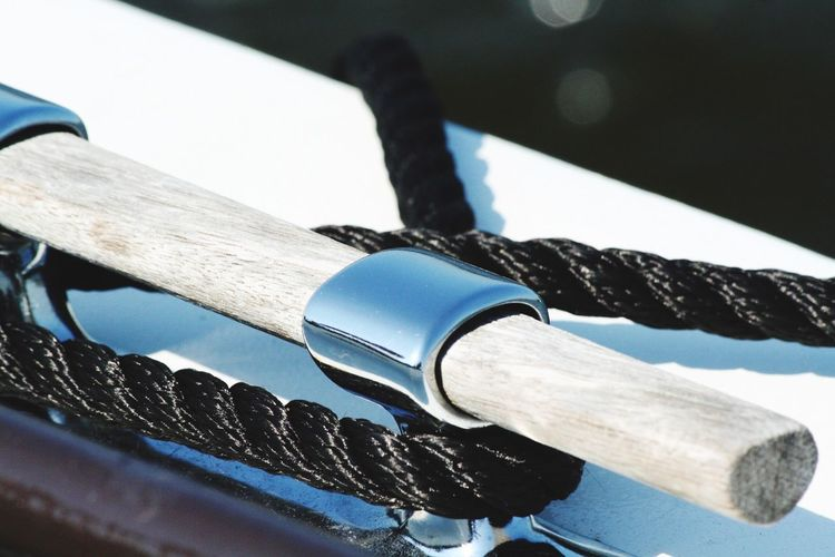 Close-up of rope tied to cleat of boat